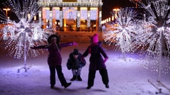 Three children dance together among illumination on winter evening Stock Footage