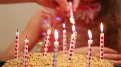 Light candles on sweet cake and girl out of focus at birthday Stock Footage
