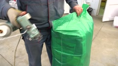 Warehouse worker sewing up green plastic bag with goods 4K video Stock Footage