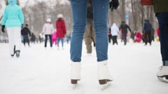 Legs of girls in jeans skating  in winter park during snowfall Stock Footage