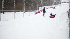 Happy people going down slope on Snow Tubes at winter day Stock Footage