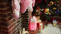 Close up of fireplace with socks and Christmas tree with presents - stock footage