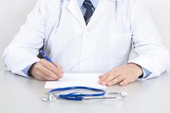 Doctor Writing on a White Sheet Stock Photos