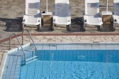 Swimming Pool and Sunbeds Stock Photos