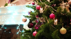 Green Christmas tree with balls and electric fireplace out of focus - stock footage