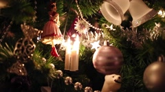 Close up of artificial Christmas tree with toy doll, bells and balls - stock footage