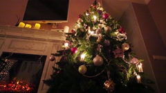 Green Christmas tree with balls, electric fireplace and tv Stock Footage