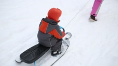 Back of woman and two children skiing with sled in forest Stock Footage