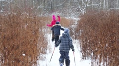 Three children on skis goes on field in direction of forest Stock Footage