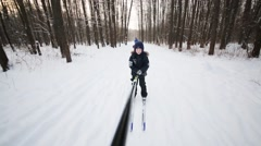 Boy goes on skis holding stick in woods and other people out of focus Stock Footage