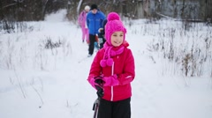 Three children and two adults rides on skis on winter day Stock Footage