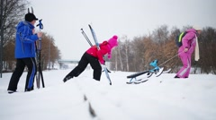 Man and girl with skis and woman with sled moving through railway Stock Footage