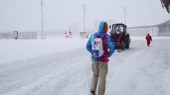 Back of going man and tractor removing snow at winter day Stock Footage