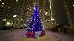 Illuminated christmas tree on playground near residential buildings Stock Footage