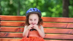 Cute little girl in blue helmet sits on bench at summer day Stock Footage