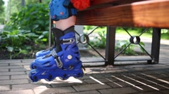 Little girl in helmet and roller skates sits on bench and laughs Stock Footage