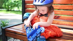 Little girl in helmet sits on bench and buttons roller skates Stock Footage