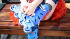 Little girl sits on bench and unbuttons roller skates Stock Footage