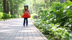 Little girl in skirt roller-blades and brakes in park Stock Footage
