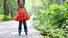 Little girl in skirt and roller-blades poses in park Stock Footage