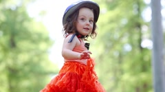 Little girl in skirt and helmet dances and poses in park Stock Footage