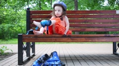 Girl sits on bench and removes protective pads for roller skating Stock Footage