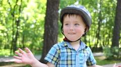 Happy cute little boy in helmet claps in summer park Stock Footage
