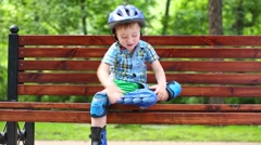 Little boy in roller-blades sits in bench and plays in summer park Stock Footage