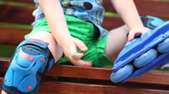 Close up of roller-blades and hands of boy on bench in summer park Stock Footage