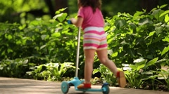 Back of little cute girl in shorts riding scooter in summer park Stock Footage