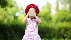 Little cute girl in flower wreath drinks milk in summer park Stock Footage