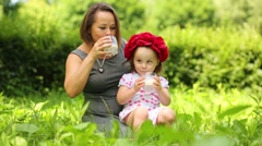Little cute girl in flower wreath and her mother drink milk Stock Footage