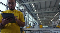 Camera pans across to create a Portrait of factory worker Stock Footage
