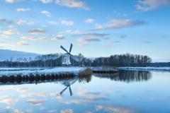 Charming windmill reflected in river water Stock Photos