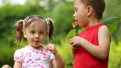 Little pretty girl and boy lick lollipops in green park Stock Footage