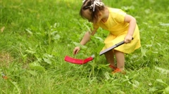 Cute little girl plays with ball and hockey stick on grass Stock Footage