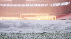 Closeup view of snow on green field in football stadium with lamps Stock Footage