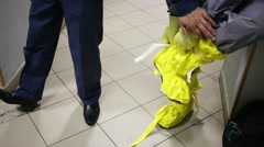Showing of protective chemical suit - disrobing of yellow shoes Stock Footage