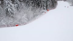 Skiers down on ski slope on track at winter day. Top view Stock Footage