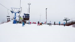 Ropeway and snowboarders at downhill in skiing sports complex Stock Footage