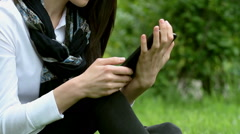 The cute young girl sitting on the grass in the park and holding a tablet - stock footage