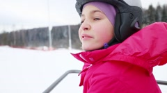 Happy cute girl in helmet moves on rope way in ski resort Stock Footage
