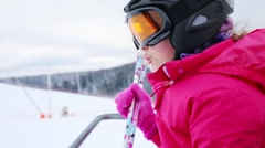 Happy cute girl in sunglasses moves on rope way in ski resort Stock Footage
