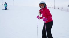 Happy cute girl in sunglasses poses on ski on slope of ski resort Stock Footage
