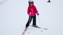 Happy girl in sunglasses poses on ski on slope of ski resort Stock Footage