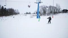 Boy quickly down on slope and girl rides at winter of sports complex Stock Footage