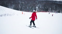 Back of woman down on slope at winter day on hill of sports complex Stock Footage