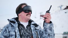 Man in ski goggles holds radio and smiles. Ropeway out of focus Stock Footage