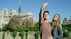 Young couple in Paris. Visiting Notre dame, Camera pans from Iconic landmark to Stock Footage