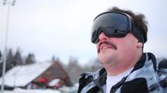 Man in ski goggles looks away at winter day in ski resort Stock Footage